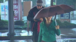 A man and woman are seen crossing a street in the rain on Saturday, Jan. 10, 2015. (Credit: KTLA)