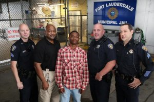 A teen and three Fort Lauderdale police officers will be commended for saving an officer's life. Jamal Rutledge, center, helped save the life of Officer Franklin Foulks in September 2014 while Foulks was booking him. (Credit: Fort Lauderdale Police Department)