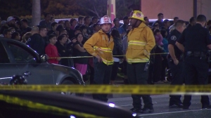 As dozens look on, firefighters and police respond to a Jan. 29, 2015, crash that killed two Banning high student siblings. (Credit: KTLA)