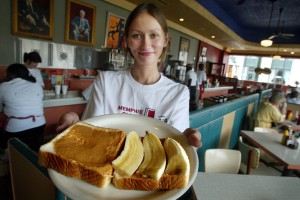Arcade restaurant waitress Julia Flowers holds a peanut butter and banana sandwich, Elvis Presley's favorite snack, on the 25th anniversary of Presley's death during Elvis Week in August 2002 in Memphis, Tennessee. (Credit: Mario Tama/Getty Images)
