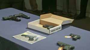 After the shooting of Jamar Nicholson, police  on Feb. 12, 2015, display replica handguns including the one -- in a box -- that Nicholson's friend was allegedly holding. (Credit: KTLA)