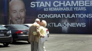 Stan Chambers kisses his wife, Gege, as they walk past a giant banner commemorating his career. He retired in 2010. (Credit: Bob Chamberlin / Los Angeles Times)