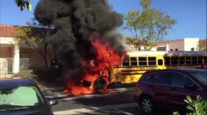 A witness's video showed a school bus engulfed in flames outside a middle school in Rancho Santa Margarita on Friday, March 27, 2015. (Credit: David Fogal)