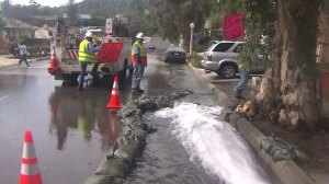 Sandbags direct water flowing through streets near the Eagle Rock Reservoir on March 16, 2015. (Credit: KTLA)