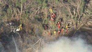Firefighters worked in heavy brush to battle a blaze in a wash in Santa Clarita on March 23, 2015. (Credit: KTLA)