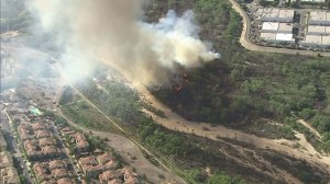 A brush fire was burning close to homes in Santa Clarita on March 23, 2015. (Credit: KTLA)