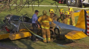 Los Angeles firefighters are seen near a plane that was piloted by Harrison Ford when it crashed at a golf course in Venice on Thursday, March 6, 2015. (Credit: KTLA)