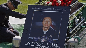 LAPD Officer Leila Ryan, who was a police academy classmate of Officer Nicholas Lee's, pays her respects during a graveside service in March 2014. (Credit: Los Angeles Times)