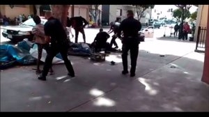 A screenshot from a bystander's video shows Los Angeles police officers struggling with a man moments before he was fatally shot on Skid Row on March 1, 2015. (Credit: Anthony Blackburn via Facebook)