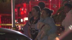 People look on as firefighters battled an apartment fire in Long Beach on March 26, 2015. (Credit: KTLA)