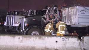Firefighters are seen near a big rig that burned at an industrial facility in South Gate on Wednesday, March 11, 2015. (Credit: KTLA)