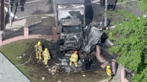 Firefighters worked after a collision burned a truck in North Hills on March 17, 2015. (Credit: KTLA)