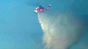 A firefighting helicopter works above a blaze in Santa Clarita on March 23, 2015. (Credit: KTLA)