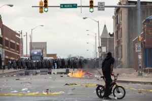 With Baltimore Police officers in riot gear lining the street, a man stands at the corner of Pennsylvania Avenue and North Avenue, April 27, 2015 in Baltimore, Maryland. Riots have erupted in Baltimore following the funeral service for Freddie Gray, who died last week while in Baltimore police custody. (Credit: Drew Angerer/Getty Images)