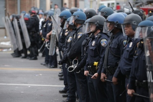 A line of Baltimore Police officers hold their ground at the corner of Pennsylvania and North avenues during violent protests following the funeral of Freddie Gray April 27, 2015, in Baltimore, Maryland. Gray, 25, who was arrested for possessing a switch blade knife April 12 outside the Gilmor Homes housing project on Baltimore's west side. According to his attorney, Gray died a week later in the hospital from a severe spinal cord injury he received while in police custody. (Credit: Chip Somodevilla/Getty Images)