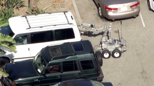 A bomb squad robot approaches a suspicious vehicle at LAX on Wednesday, April 15, 2015.