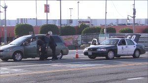 Police examine a minivan after a shooting in the Baldwin Hills area that left two men injured on Sunday, April 19, 2015. (Credit: KTLA)