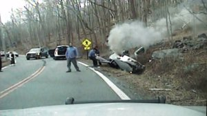 Police officers pulled a woman from an overturned car before it burst into flames on Thursday, April 16, 2015. (Credit: Kinnelon Police Department)
