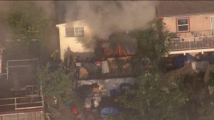 Firefighters battled a fire at a home in Lincoln Heights on Monday, April 27, 2015. (Credit: KTLA)