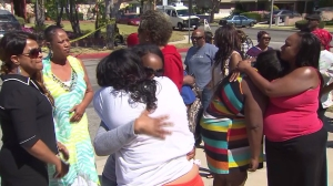 People could be seen grieving after a couple died in an apparent murder-suicide in Carson on April 12, 2015. (Credit: KTLA)