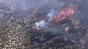 Firefighters were working in brush to combat a blaze in Granada Hills on April 27, 2015. (Credit: KTLA)