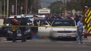 Two people were dead after a car-to-car shooting that prompted a police officer to open fire in Hawthorne on April 1, 2015. (Credit: KTLA)