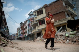 People walk past the rubble of destroyed buildings following a second major earthquake May 13, 2015, in Kathmandu, Nepal. (Credit: Jonas Gratzer/Getty Images)