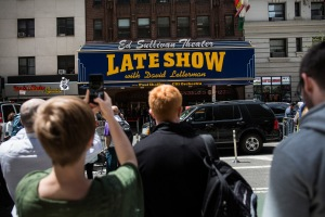 Fans of David Letterman, members of the media, security agents and passersby gather around the entrance to the Ed Sullivan Theater, where 'The Late Show with David Letterman' is filmed, on May 20, 2015, in New York City for its last episode.  (Credit: Andrew Burton/Getty Images)