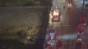 Officials are seen at the scene of a crash off the 710 Freeway in Long Beach on Friday, May 1, 2015. (Credit: KTLA)