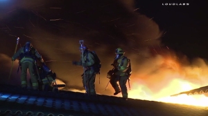 Four firefighters are pictured before falling through a roof in Cudahy while battling a fire on May 22, 2015. (Credit: Loudlabs)