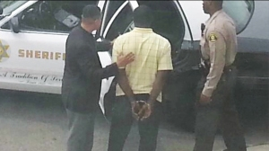 A photograph tajen by a neighbor showed Titus Chidi Ebubechukwu being arrested outside his Lancaster home.