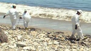Workers clean up Refugio State Beach on May 20, 2015, a day after a massive oil spill. (Credit: KTLA)