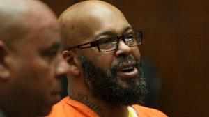 "Former rap mogul Marion ""Suge"" Knight, in orange jail attire, appears with attorney Matthew Fletcher in Los Angeles criminal court April 8, 2015. (Credit: Irfan Khan / Los Angeles Times)"