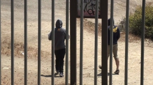 "Two people are seen through a fence as they explore ""Sunken City"" in San Pedro. (Credit: KTLA)"