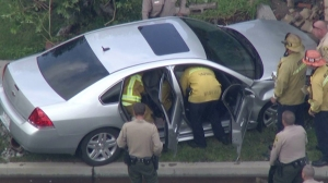 Firefighters looked into a vehicle after a deputy-involved shooting in Cerritos on May 7, 2015. (Credit: KTLA)
