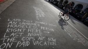 A man on a bike pedals past a messages written in chalk near the site of a May 5, 2015, fatal LAPD officer-involved shooting of a homeless man in Venice. (Credit: Irfan Khan / Los Angeles Times)