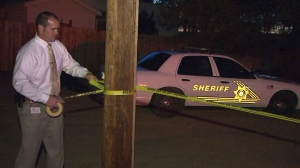 Investigators are seen in Adelanto on June 11, 2015, after a 7-year-old boy was shot and killed. (Credit: KTLA)