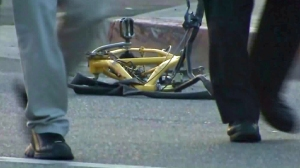 A mangled bike remains on the scene of a fatal hit-and-run crash in Highland Park on June 26, 2015, as LAPD investigators walk by. (Credit: KTLA)
