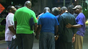 Community members gathered in a prayer circle just down the street from the shooting scene on Wednesday, July 17, 2015. (Credit: CNN)