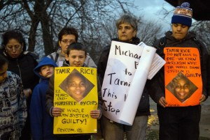 People display sigs at Cudell Commons Park in Cleveland, Ohio, Nov. 24, 2014, during a rally for Tamir Rice, a 12-year-old boy shot by police the previous day. (Credit: ORDAN GONZALEZ/AFP/Getty Images)