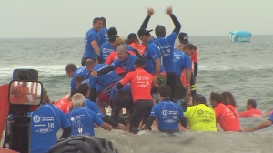 Sixty-six surfers are seen climbing on top of a large surf board in Huntington Beach on June 20, 2015, in an attempt to beat the Guinness World Record for most surfers to ride a wave. (Credit: KTLA)