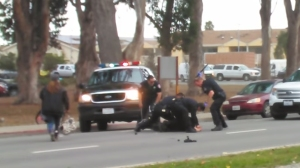 A screenshot from a cellphone video shows Salinas police officers subduing an assault suspect on Friday, June 5, 2015. (Credit: Richard Boxing/via YouTube)