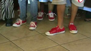 Supporters of Tavin Price wore red shoes at a June 23, 2015, news conference where police announced arrests in his killing. (Credit: KTLA)