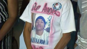 Tavin Price's mother Jennifer Rivers wears a shirt with his likeness at a June 23, 2015, news conference announcing arrests in his death. (Credit: KTLA)