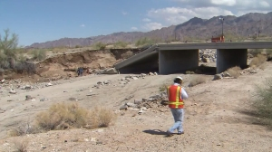 A worker walks near a collapsed 10 Freeway bridge in desert center on July 20, 2015. (Credit: KTLA)