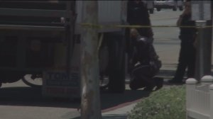 Santa Ana police worked to get the victim's bicycle out from beneath the box truck which struck her on July 13, 2015. (Credit: KTLA)