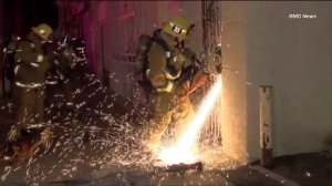 A firefighter uses an electrical saw to open a door at a South L.A.-area church where a fire broke out on Thursday, July 9, 2015. (Credit: RMG News)