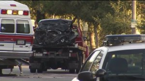 An ambulance and a Jaguar sedan are scene on a Pasadena street after colliding on Saturday, July 11, 2015. One man was killed and three other people were injured, police said. (Credit: KTLA)
