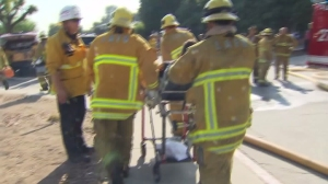 Firefighters rush one of their own away from the scene of a blaze that burned a Glassell Park church on July 7, 2015. Two firefighters were injured. (Credit: KTLA)