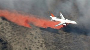 A plane makes an aerial drop in the fight against the North Fire on Friday, July 17, 2015. (Credit: KTLA)